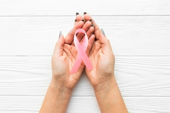 Hands with pink ribbon over timber background