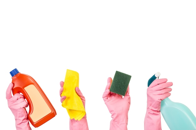 Hands with pink rubber gloves holding cleaning product bottles and cleaning elements on a white background