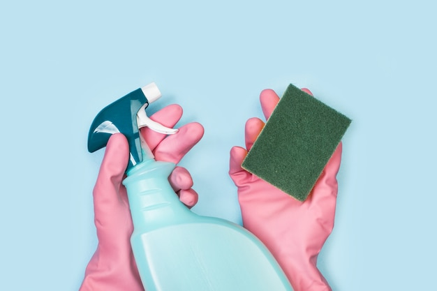 Hands with pink rubber gloves holding a cleaning sponge and a cleaning product sprayer on a light blue background