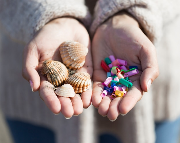 Hands with plastic and shells