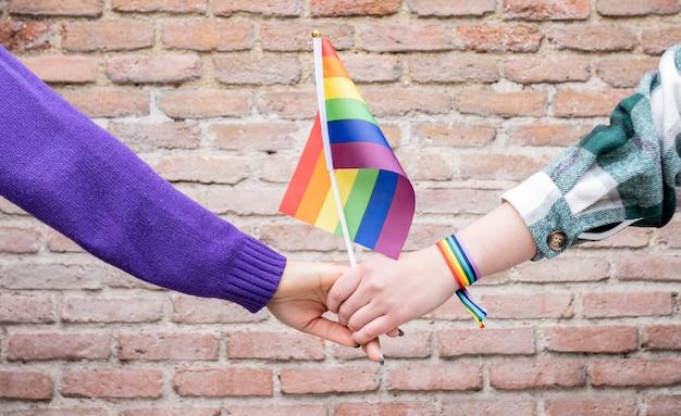 虹の腕章ゲイプライドと旗を持つ手