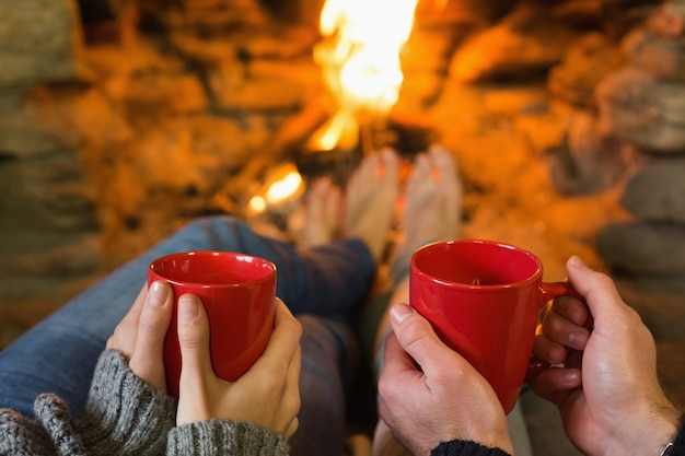 Hands with red coffee cups in front of lit fireplace