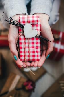 Mani con un regalo rosso e bianco con un cuore