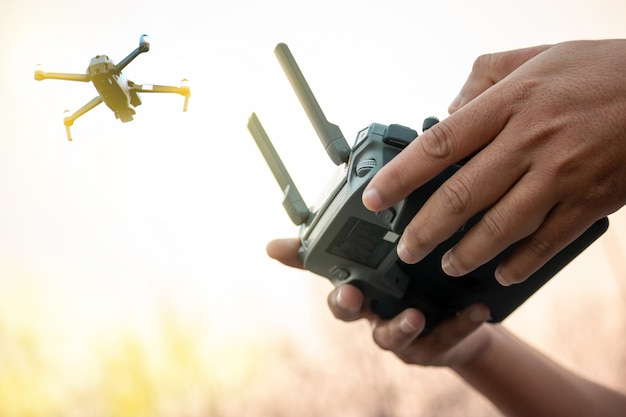 Hands with remote controller of drone outside.