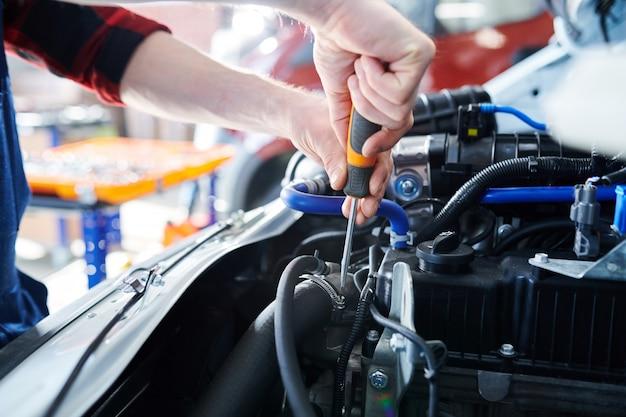 修理作業中に車のエンジンのボルトを固定しながらドライバーを使用して修理工と手