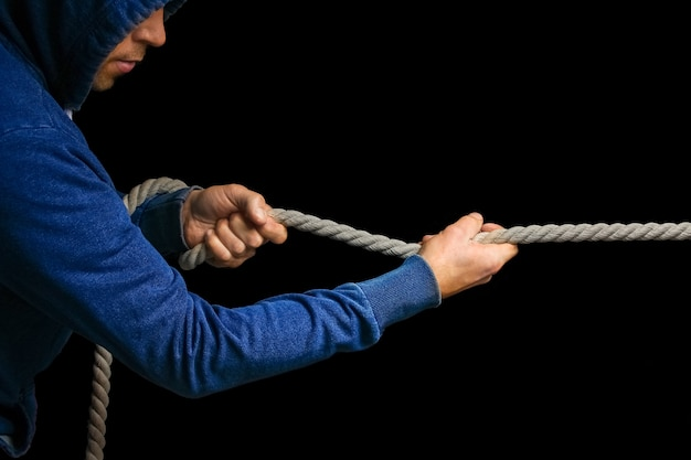 Hands with a rope on a black background. a man pulls a rope wrestling. drag the business to your side.