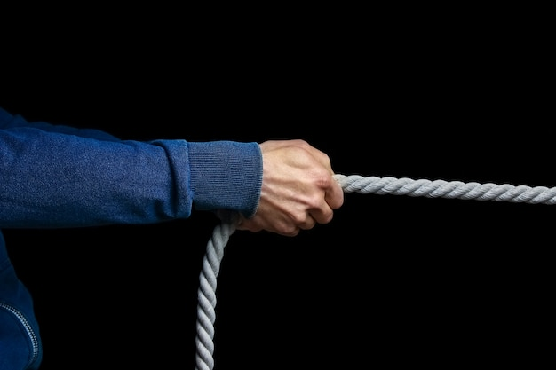 A hands with a rope on a black background. a man pulls a rope wrestling.
