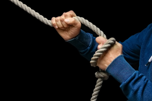 A hands with a rope on a black wall. a man pulls a rope wrestling. drag the business to your side.