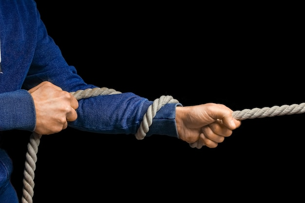 Hands with a rope on a black wall. a man pulls a rope wrestling. drag the business to your side.