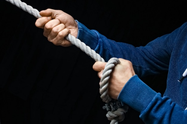 Hands with a rope on a black wall