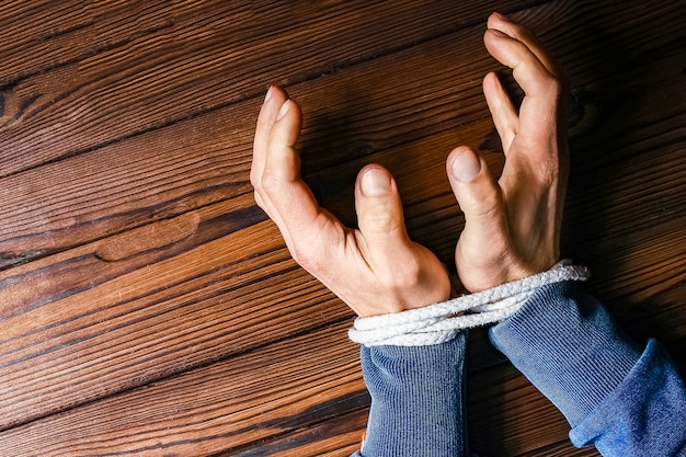 Hands with a rope on a wooden background