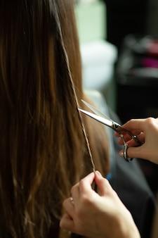 Руки с ножницами отрезают прядь чужих волос брюнетки в салоне красоты крупным планом