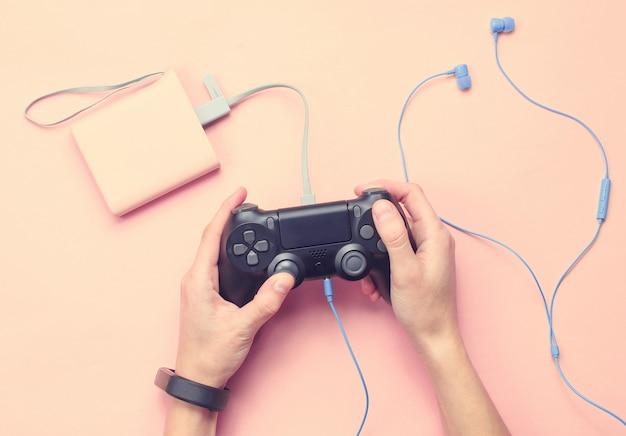 Руки с умным браслетом используют геймпад