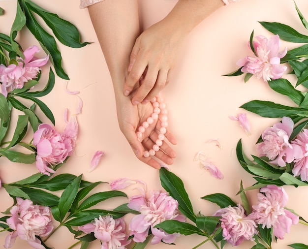 Hands with smooth skin and a bouquet of pink peonies