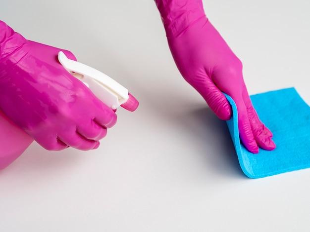 Руки с хирургическими перчатками и очищающей поверхностью