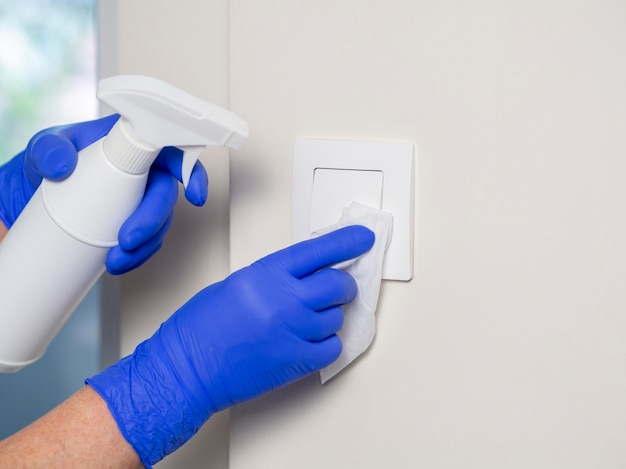 Hands with surgical gloves cleaning light switch