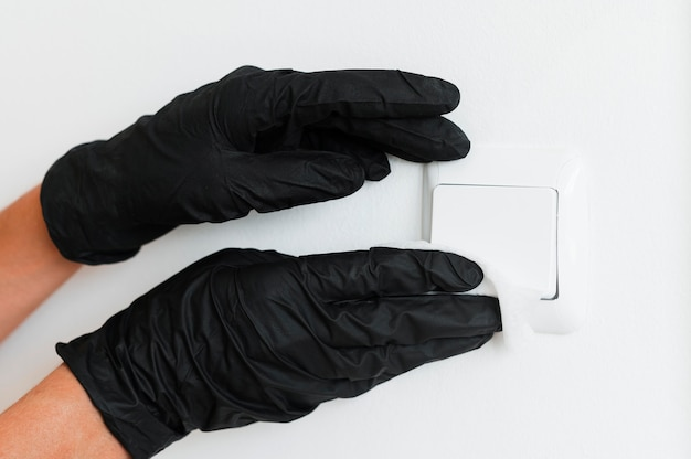 Hands with surgical gloves disinfecting light switch