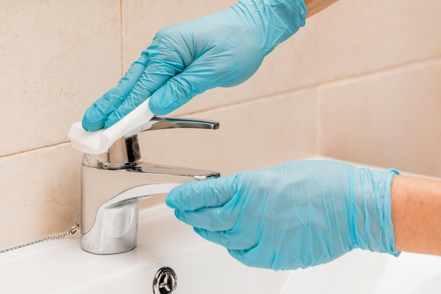 Hands with surgical gloves disinfecting sink