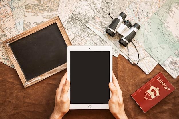 Руки с планшетом на столе с картами