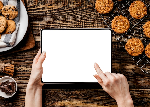 Hands with tablet and delicious cookies beside