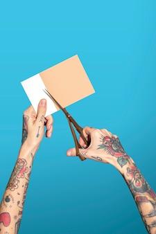 Руки с татуированными ножницами и ножницами для резки бумаги