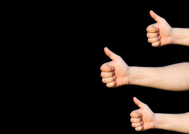 親指を立てた手。サインのように。黒の背景に分離。