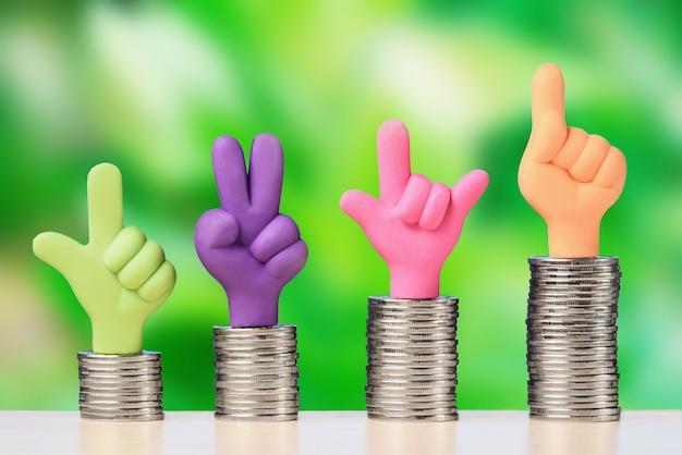 コインの山の上を親指で手。投資の成長と金融の概念。