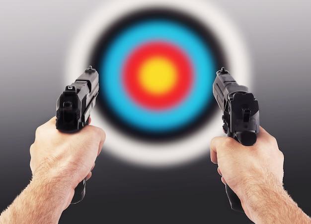 Руки с двумя пистолетами против красочной стрельбы