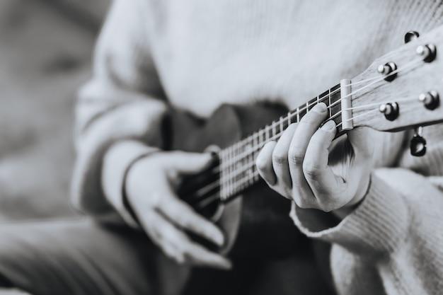 Руки с укулеле крупным планом черно-белое фото