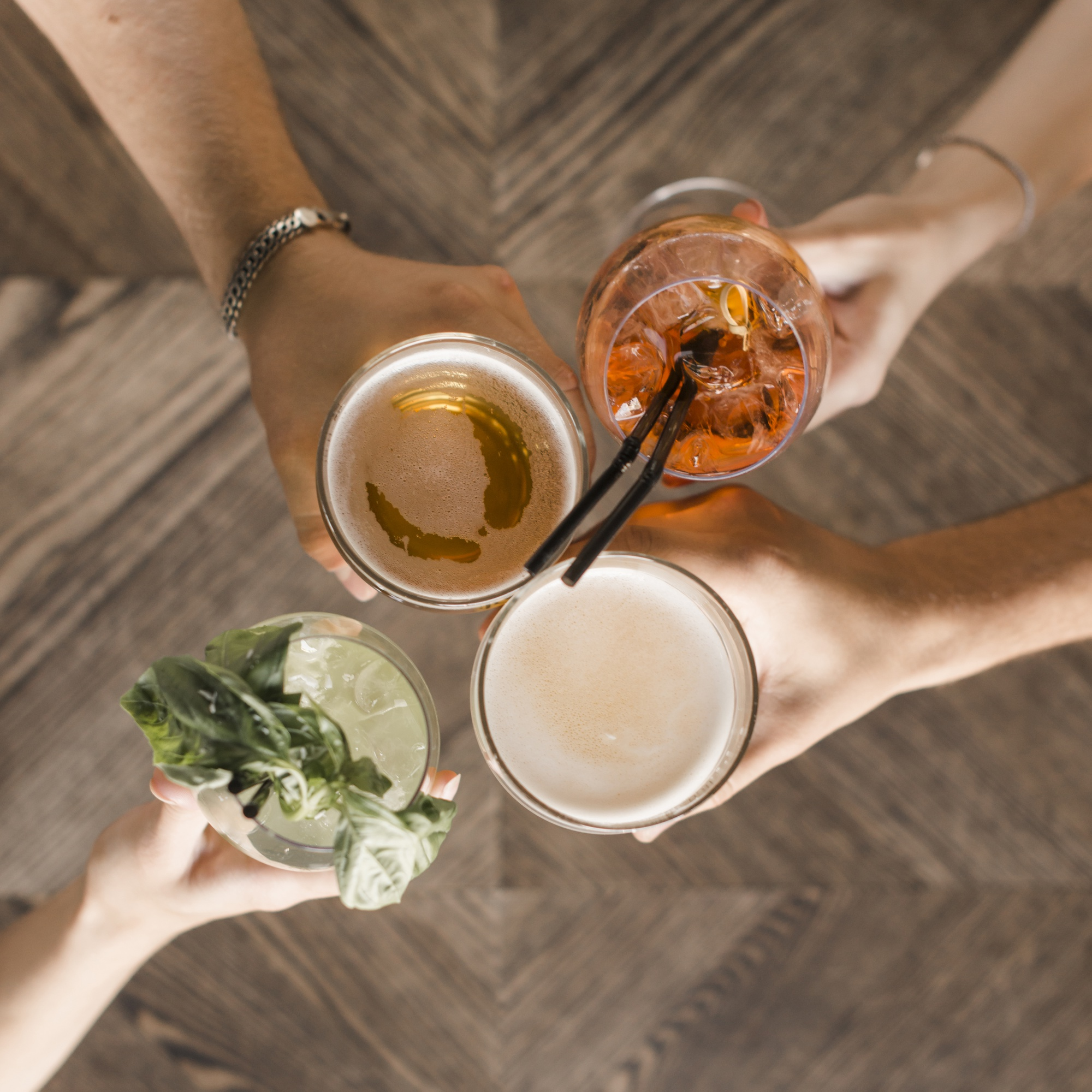 Hands with vivid drinks toasting