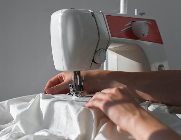 Руки с белой хлопчатобумажной тканью работают в процессе работы швейной машины с тканью