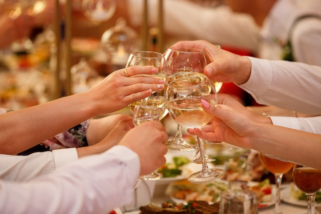 Hands with wine glasses clinking at party