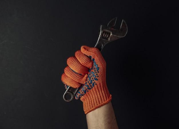 작업 장갑과 손에 검은 배경에 렌치를 잡고있다. 산업 노동자