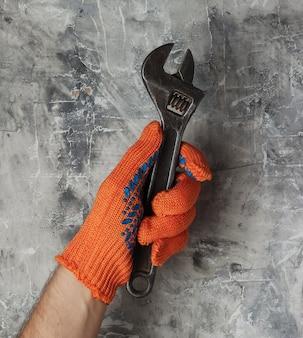작업 장갑과 손에 회색 콘크리트 배경에 렌치를 잡고있다. 산업 노동자