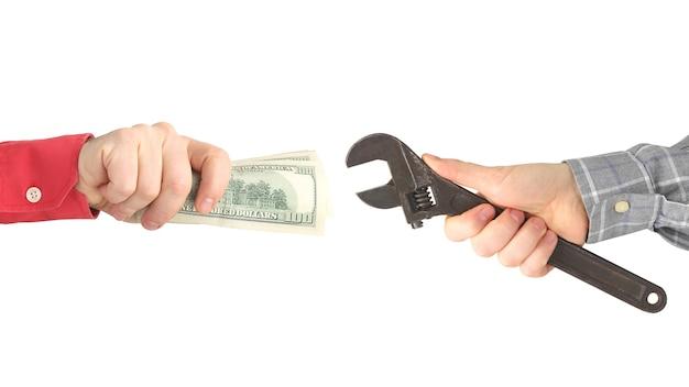白い背景の上の作業ツールとお金を持つ手。給料。ビジネス関係。