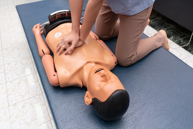 Hands of a woman are seen on a mannequin during an exercise of resuscitation (cpr).