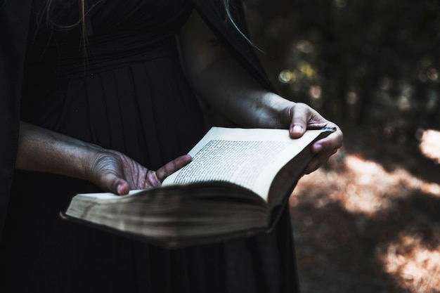 Hands of woman in black dress and cloak holding opened book