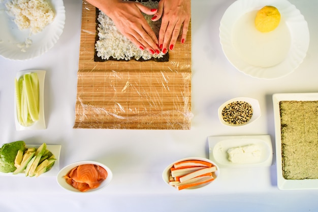 Hands of woman chef filling japanese sushi rolls with rice on a nori seaweed sheet.