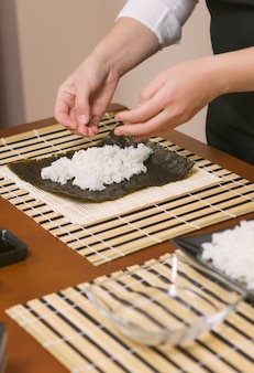 Hands of woman chef filling japanese sushi rolls with rice on a nori seaweed sheet