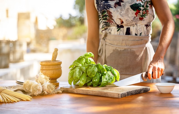 Hands of woman chopping green basil at kitchen table in a garden outdoor
