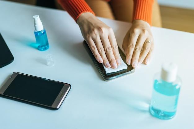 Руки женщины чистят грязный мобильный телефон на экране, профилактические меры против коронавируса