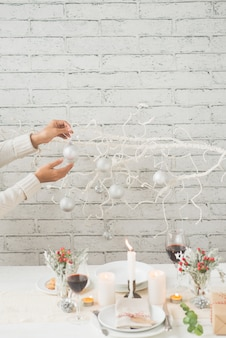 Hands of woman decorating tree branch with baubles next to tastefully arranged christmas table