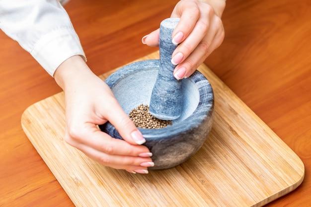 Hands of woman grinding pepper in mortar
