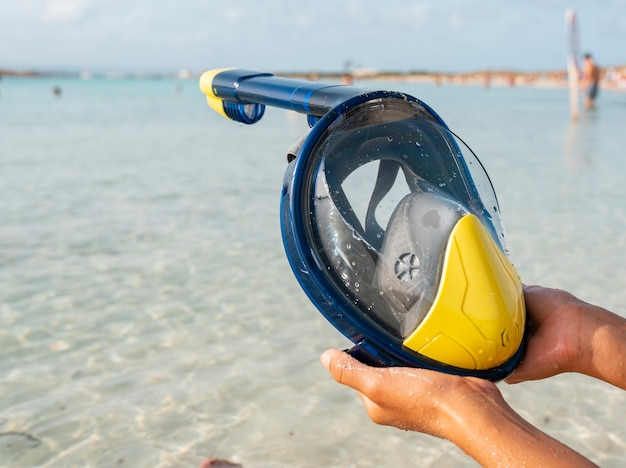 Hands of a woman hold a snorkel goggles, vacation concept