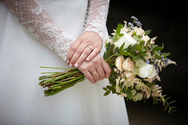 Hands of a woman holding a bouquet of flowers