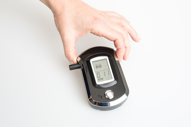 Hands of woman holding a digital alcohol breath tester