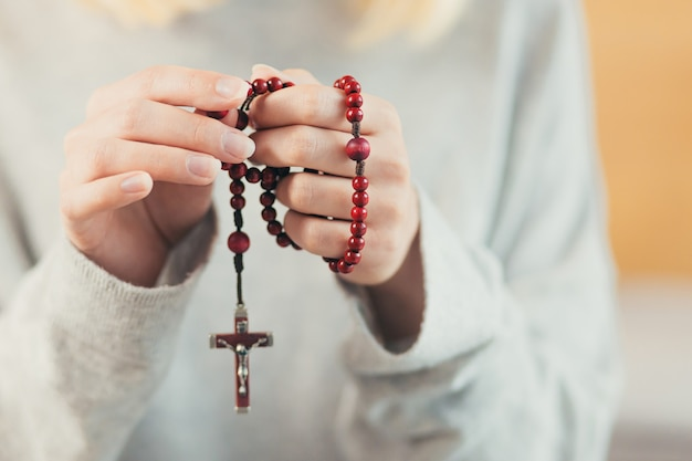 Hands of a woman holding a rosary