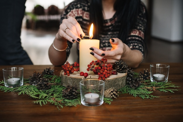 Hands of woman lighting a candle