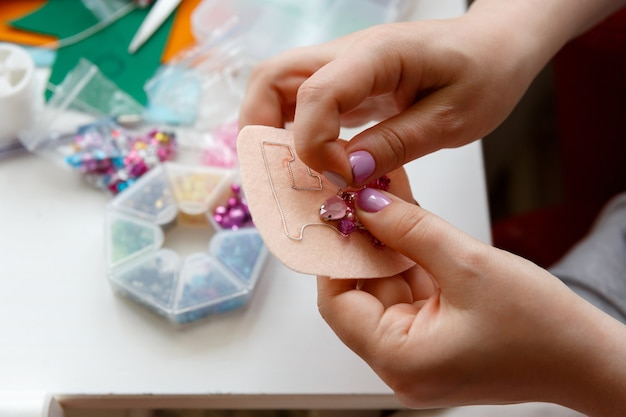 Руки женщина делает украшение броши из розового бисера и кристаллов