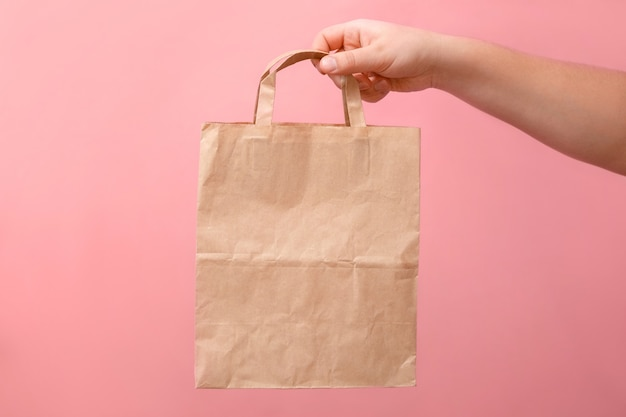 In hands of woman paper bag on pink background